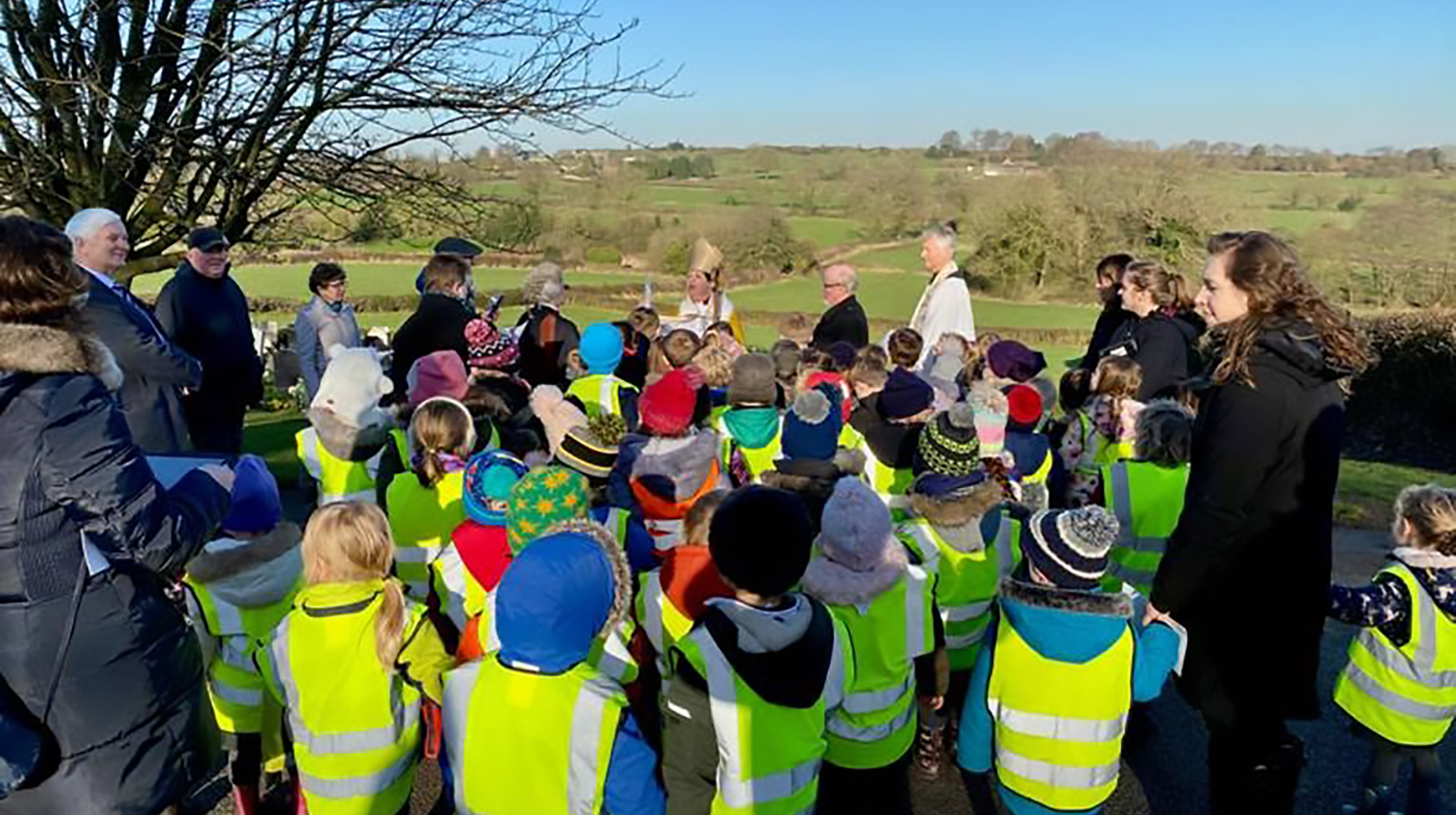 Bishop Jan and local schoolchildren at Crich graveyard