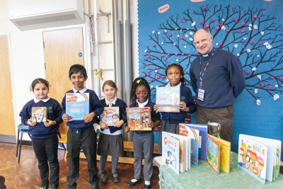 Revd Andy Bond presents children at St James School, Derby, with their new Christian story books